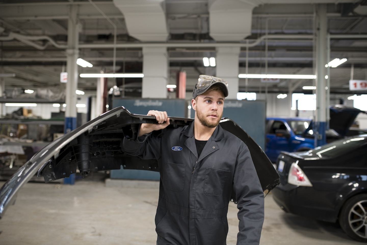 Mechanic carrying bumper through body shop